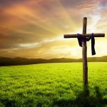 A wooden cross draped in a purple robe, standing in a grassy field beneath a beautiful sunrise.